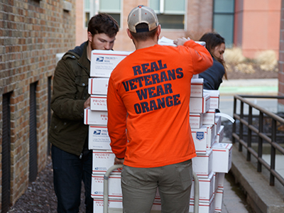 "Three people, including one in a ""Real Veterans Wear Orange"" T-shirt, pushing a dolly of packages"