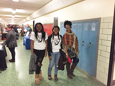 Three girls walking down school hallway, two wearing MLK T-shirts