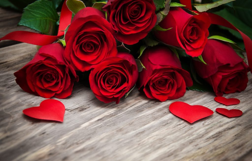 red roses with hearts on a wooden table