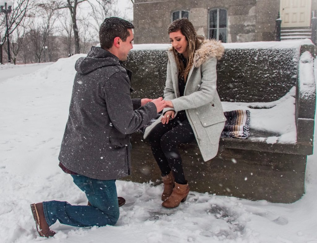 man kneeling to propose in front of woman