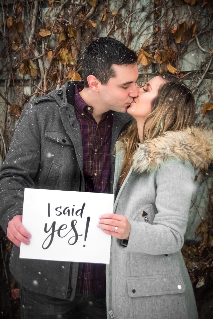 "a man and woman kissing holding sign that says ""I said yes!"""