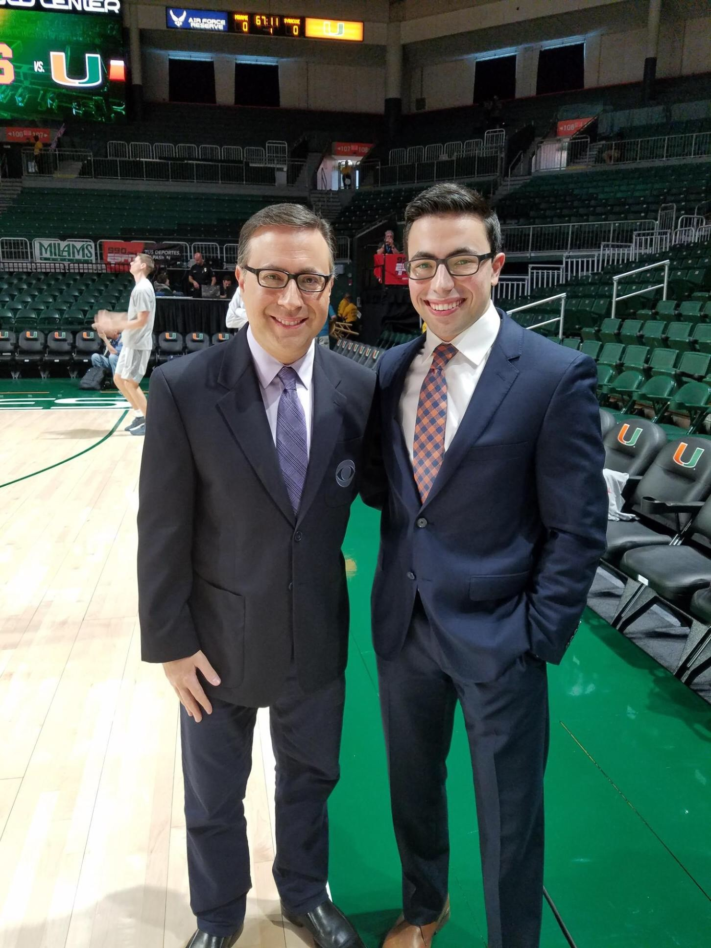 Ian Eagle stands next to his son Noah on the Miami basketball court. Both men are wearing suits and smiling. Both are wearing glasses