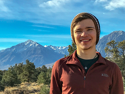 Garet Blair in knitted cap against background of mountains