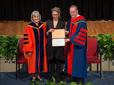 Professor holding award between Chancellor and vice chancellor