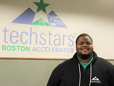 Josh Aviv posing in front of sign that says techstars Boston Accelerator