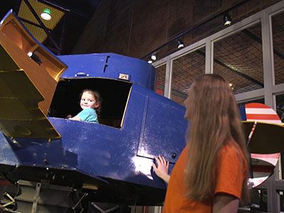 child in cockpit of flight trainer, with mother looking on