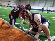 Two men's lacrosse players, each on one knee, during a faceoff
