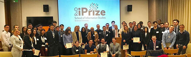 Competitors and judges at the RvD iPrize competition--dozens of people standing and sitting in front of a screen that read RvD Prize, School of Information Studies