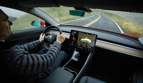 dashboard of Tesla Model 3, with person's hands on the dashboard