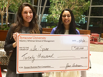 two young women holding big check