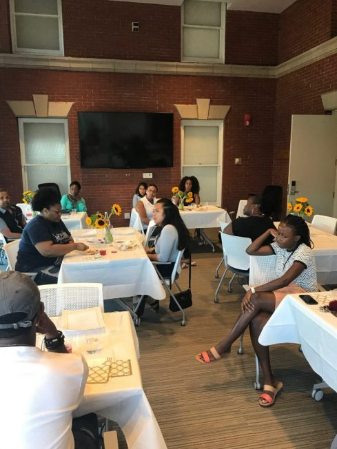 Students sit at set dinner tables for McNair Scholars program in Sims Hall
