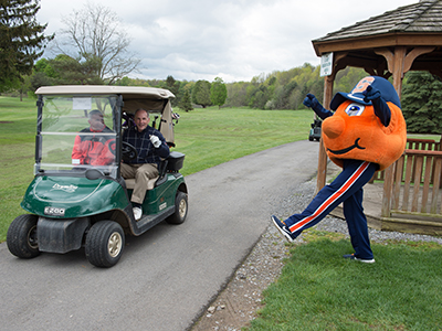 Two men in golf cart, with Otto acting surprised along the side of the road
