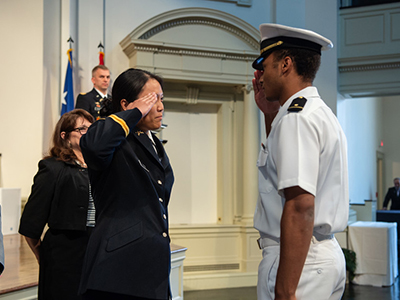 Female cadet and male officer saluting each other