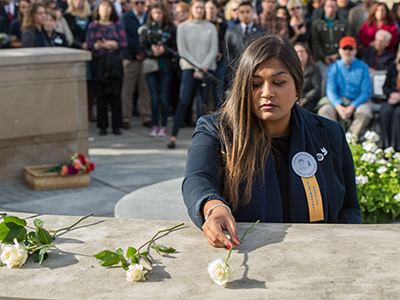 Student laying a white rose on the Remembrance Wall