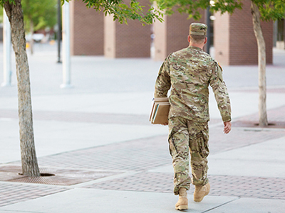 man in fatigues from rear, walking across college  campus