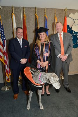 graduate in cap and gown flanked by two other adults and a dog