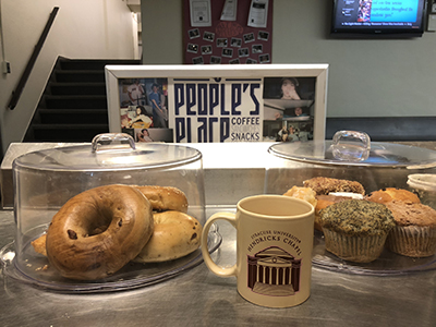"bagels, coffee cup and ""People's Place"" sign"