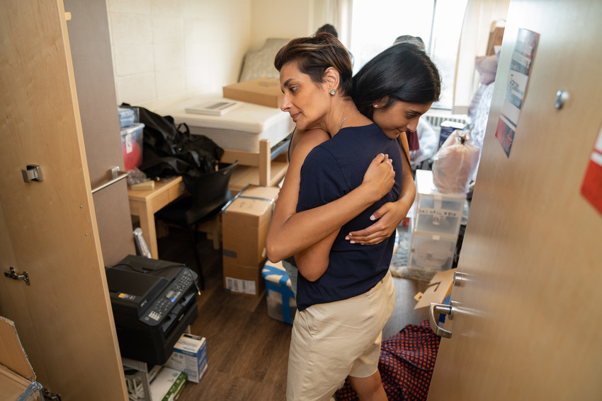 a woman hugs a younger woman in a dorm room