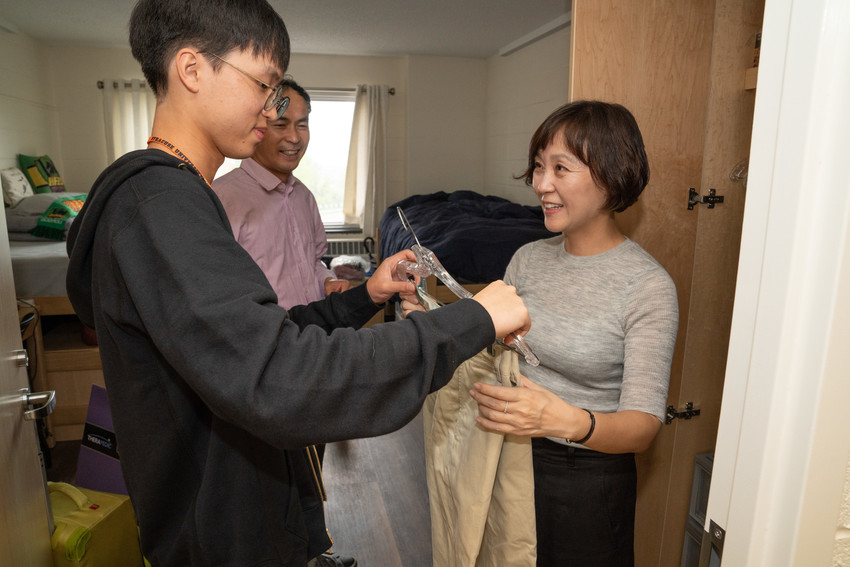 a woman and a young man hold up a hanger with clothing