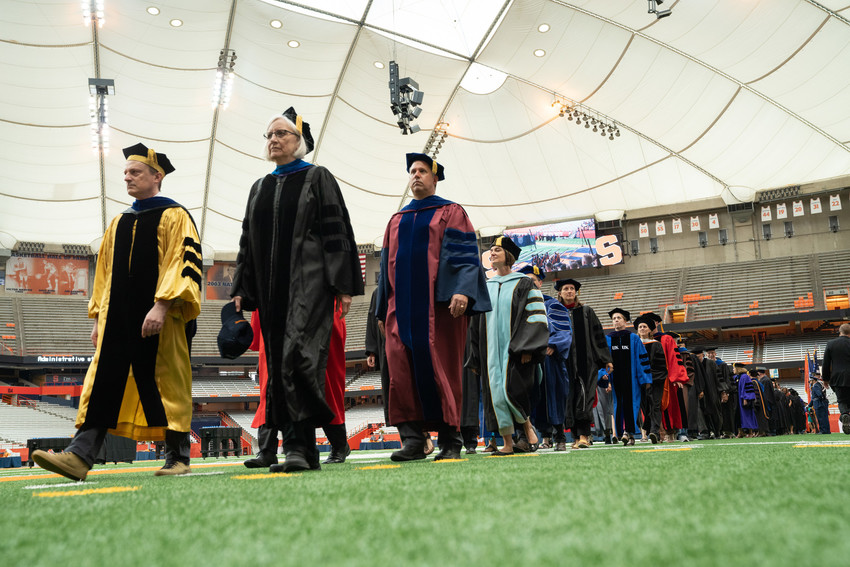 people in academic robes walk into Dome