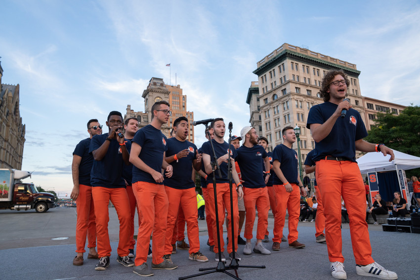 a group of men singing on a city plaza
