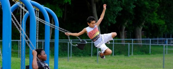 Child jumping off of a swing.