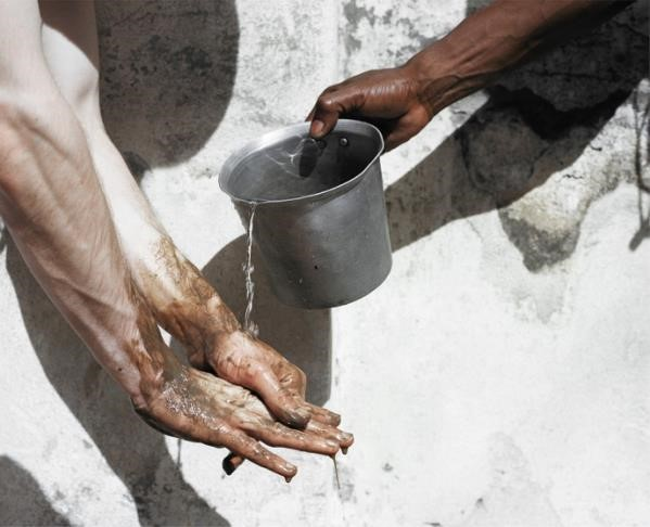person pouring water over another person's hands