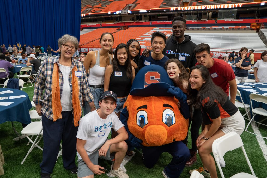 Students and Otto the Orange at the International Student Welcome Dinner.