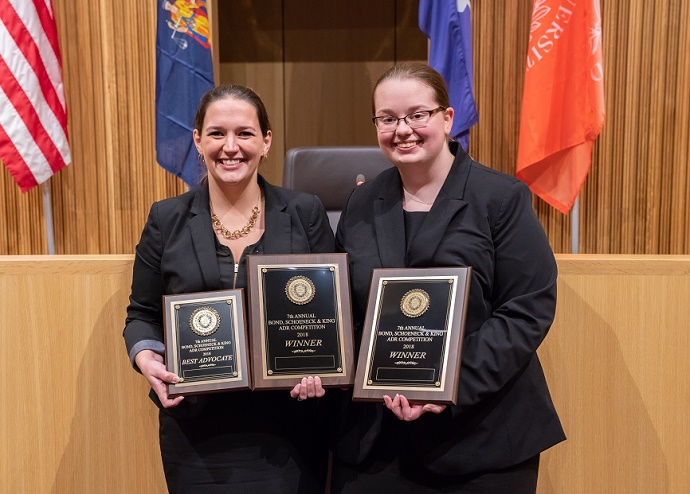 two women standing holding plaques