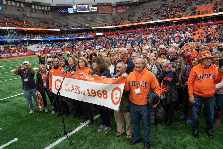 group of people with banner on football field