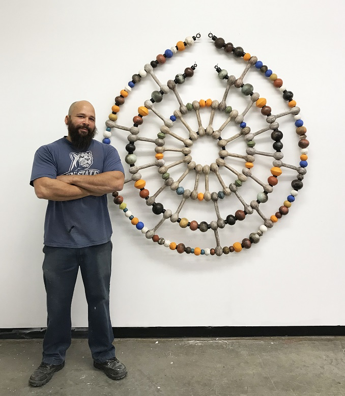man standing next to artwork
