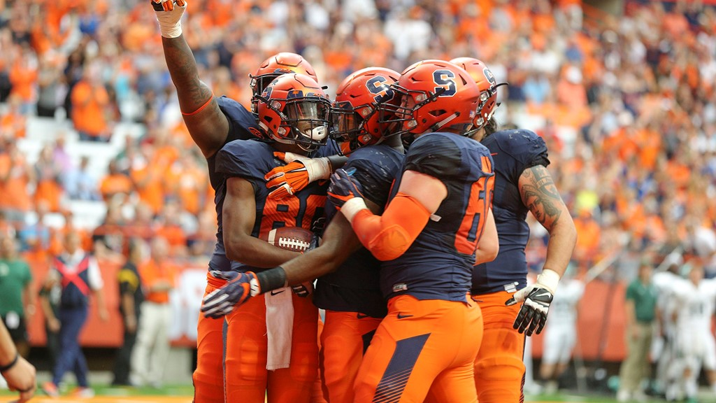 SU football players huddle in celebration on the field.