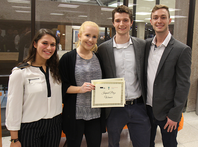 four people standing holding certificate