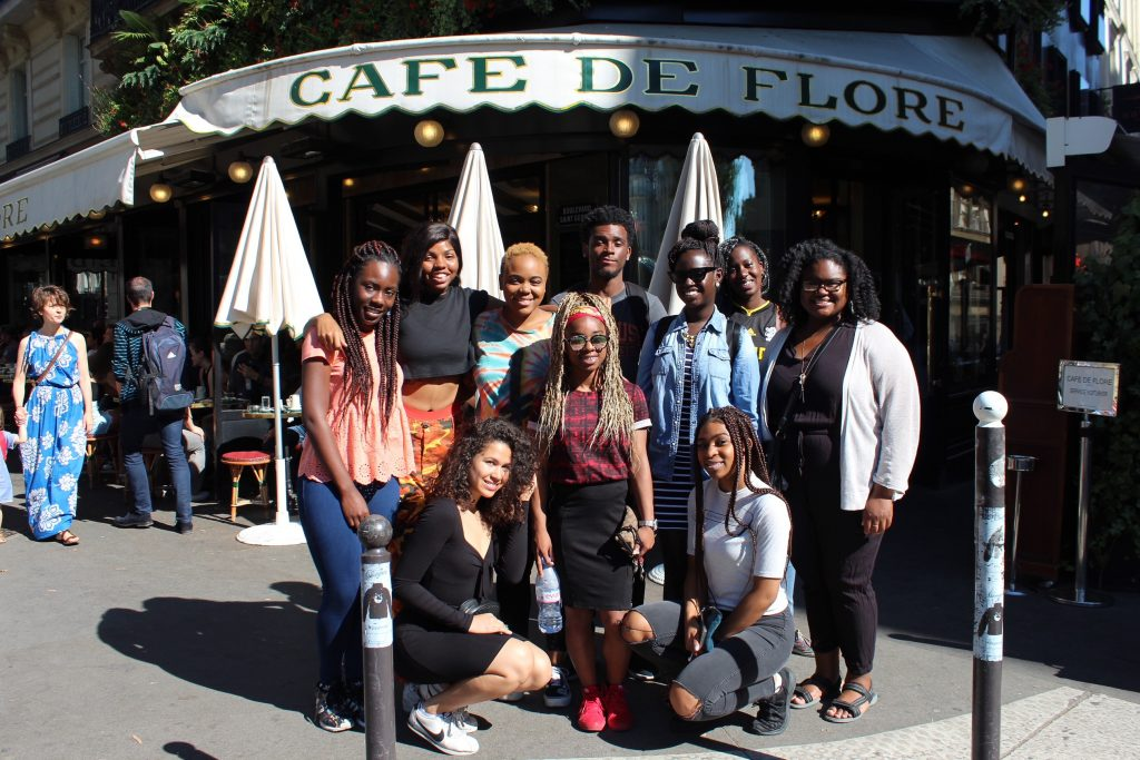 Students pose outside a Parisian café.