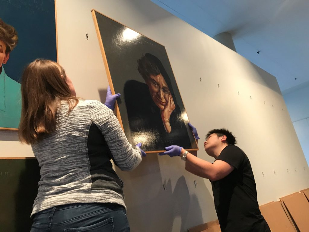 Students hang Robert Shetterly's portrait of Dorothea Lange.