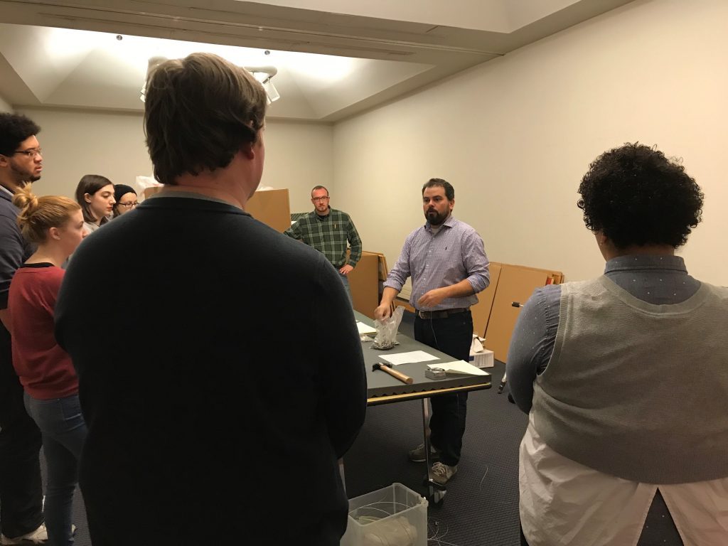 Andrew Saluti, assistant professor and program coordinator in the museum studies graduate program, instructs museum studies students on the hanging of the exhibition.