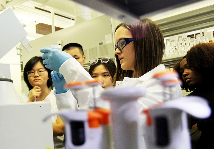 woman working in lab surrounded by a few people