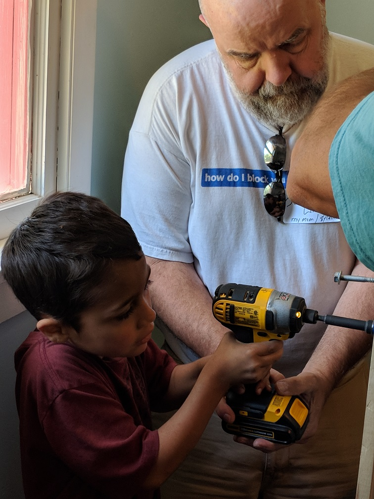 man helping boy using power tool to build bed