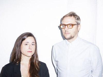 Emily Abruzzo and Gerald Bodziak look seriously at camera, Abruzzo in black and Bodziak in white