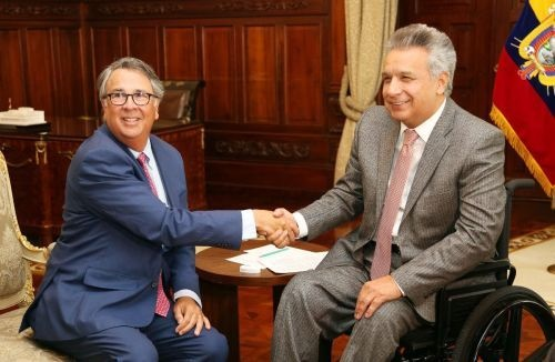 two men seated shaking hands