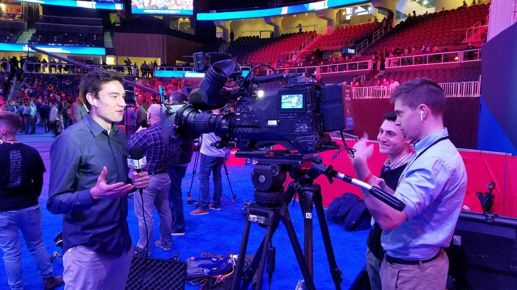 Drew Carter '19 does a live shot for CitrusTV at Super Bowl Opening Night in the State Farm Arena in Atlanta. Behind the camera are Jonah Karp '20 (center) and Jackson Ajello '19. (Photo by Dennis Deninger)