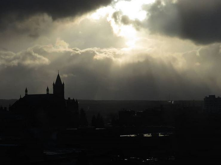 sun breaking through clouds over campus