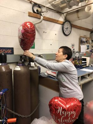 Linda Owens, coordinator of the Hugs from Home program, prepares balloon bouquets.