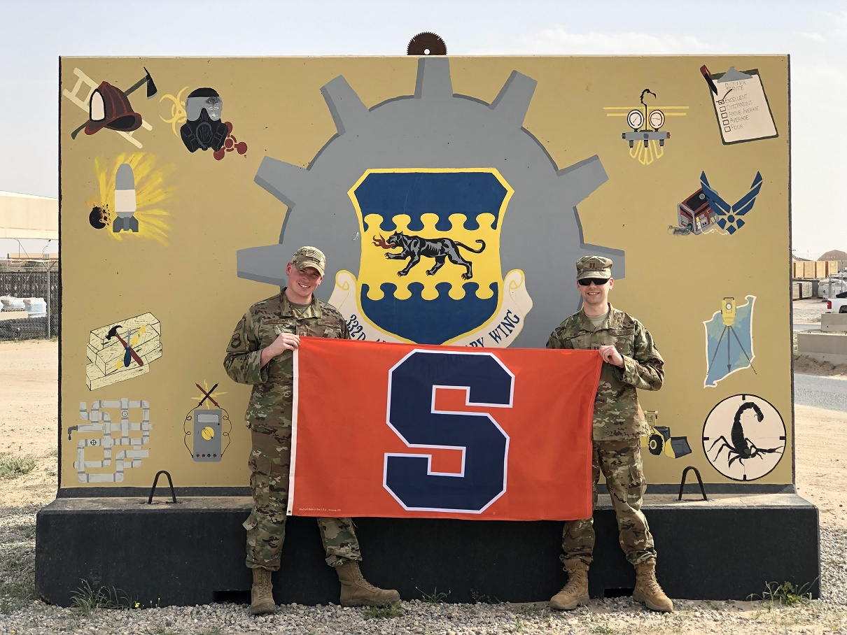 two men in uniforms holding flag with S