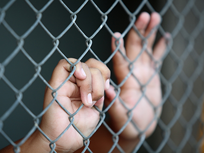 child's hands on chain link fence