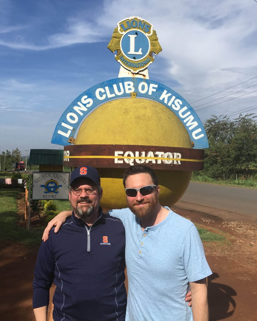 Tucker with Lou Berends, director of strategic and international partnerships at Syracuse Abroad, standing on the equator in Kisumu, Kenya, in March 2018.