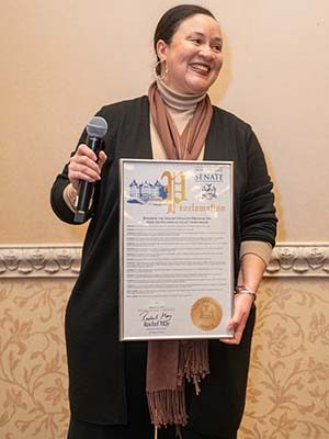 Nicole Watkins smiling to side holding proclamation given by Senator Rachel May.