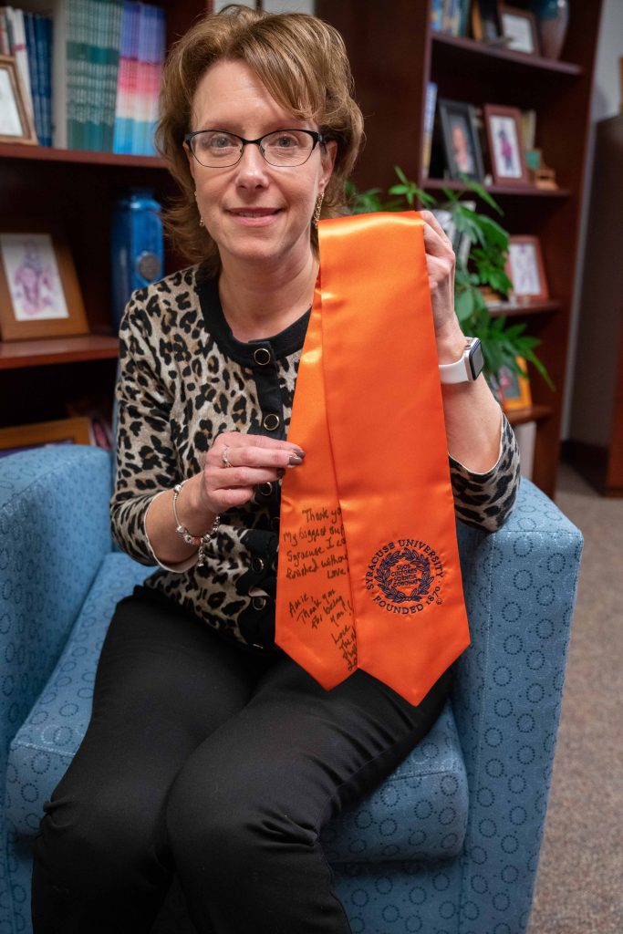 "Amie Redmond displays a stole presented to her last May by a graduating student whom she had helped through a family tragedy. Written on it are messages from the student (""Thank you for being my biggest support at Syracuse. I couldn't have finished without you."") and the student's mother (""Amie, thank you for being you."")."