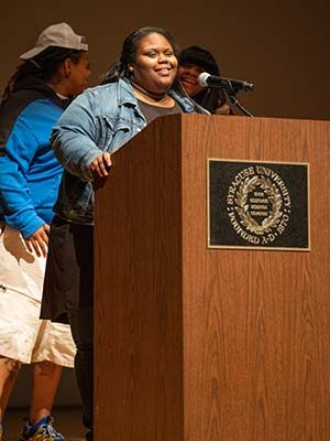 SaQuota Reaves stands smiling at podium with Syracuse University seal on front of podium
