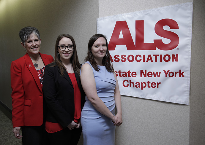 three women standing in front of sign that states ALS Association